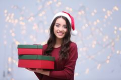Attractive young lady in Christmas hat holding gift boxes. On blurred background Stock Photography