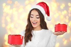 Attractive young lady in Christmas hat holding gift boxes. On blurred background Royalty Free Stock Photos