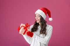 Attractive young lady in Christmas hat and red gloves holding gift box Royalty Free Stock Photos