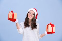 Attractive young lady in Christmas hat and red gloves holding gift boxes Royalty Free Stock Image