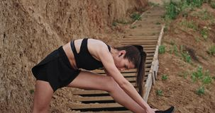 Attractive young lady concentrated exercises the relaxed stretching poses enjoying the fresh air outside on wooden steps.  stock video footage