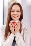 Attractive young lady with a cup of drink Stock Photography