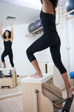 Attractive young lady doing pilates. An attractive young lady performing a Pilates exercise with resistance from equipmant in a Pilates studio. Composition with Royalty Free Stock Photography