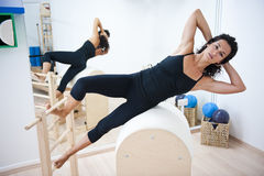 Attractive young lady doing pilates. An attractive young lady performing a Pilates exercise with resistance from equipmant in a Pilates studio. Back reflection Royalty Free Stock Photos