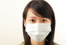 Attractive young lady with a face mask. To protect against flu Royalty Free Stock Photo