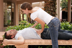 Attractive young lady getting ready to massage her. Man's chest at tropical resort Royalty Free Stock Photo