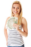Attractive young lady holding cash and happy smiling over white background. Stock Photography