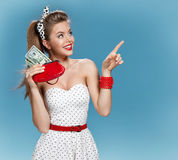 Attractive young lady holding cash and shows forefinger. Shopping concept Royalty Free Stock Photography