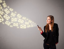 Attractive young lady holding a phone with message icons Stock Images