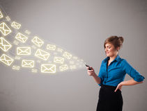 Attractive young lady holding a phone with message icons Stock Photos