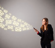 Attractive young lady holding a phone with message icons Royalty Free Stock Photo
