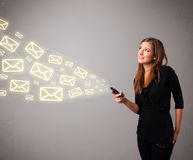 Attractive young lady holding a phone with message icons Stock Photography