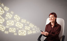 Attractive young lady holding a phone with message icons Royalty Free Stock Photography