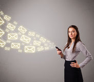 Attractive young lady holding a phone with message icons. Attractive young lady standing and holding a phone with message icons Stock Images