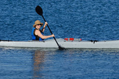Attractive young lady in a kay. An attractive young lady is paddling along in tropical waters of Mission Bay, San Diego, California Stock Photography