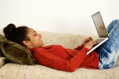 Attractive young lady lying on sofa typing on laptop Royalty Free Stock Photography