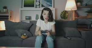 Attractive young lady playing video game at home at night then clapping hands. Attractive young lady is playing video game at home at night then clapping hands stock footage