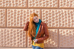 Attractive young lady posing in front of the pink brickwall Royalty Free Stock Photo
