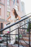Attractive young lady. Posing on the street near the handrail standing on the steps dressed in a long dress stock images