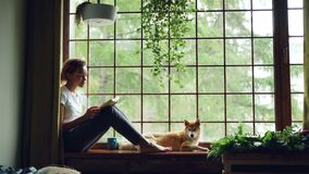 Attractive young lady is reading book sitting on windowsill in the house together with adorable puppy. Large window stock video footage