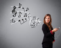 Attractive young lady singing and listening to music with musica Stock Photos