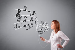 Attractive young lady singing and listening to music with musica. L notes getting out of her mouth Stock Photos