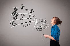 Attractive young lady singing and listening to music with musica Stock Photography