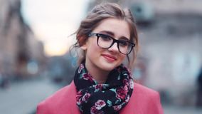 Attractive young lady in a stylish look and fashionable accessories walking and looking right towards the camera in the. City street. Gorgeous woman. Happy stock footage