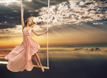 Attractive young lady on a swing above the sea Royalty Free Stock Photos