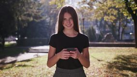 An attractive young lady using a phone in town. Medium shot stock images