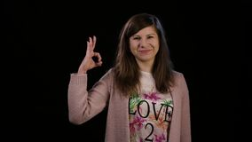A Lady Making an Ok Gesture. An attractive young lady wearing a pink sweater makes an ok gesture against a black background. Medium shot Royalty Free Stock Image