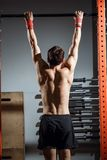Attractive young male adults doing pull ups on bar in cross fit training gym. Fitness toes to bar man pull-ups bars workout exercise at gym Stock Photography