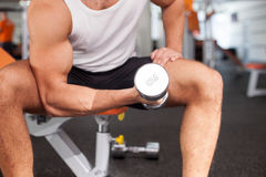Attractive young male athlete is lifting weights. Close up of body of sportsman training in fitness center. He is sitting on bench. The man is raising dumbbell l Stock Photo