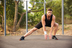 Attractive young male athlete stretching his legs. Outdoors Royalty Free Stock Photos