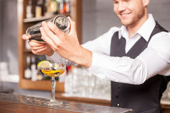 Attractive young male barman is preparing alcohol Stock Image
