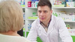 Attractive young male chemist smiling, talking to his senior customer stock footage