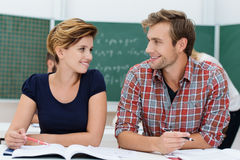 Attractive young male and female students. Attractive young male and female college students sharing a desk together sit in the classroom discussing a project Royalty Free Stock Images