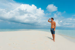 Attractive young male looks away standing on beautiful beach wit Stock Photos