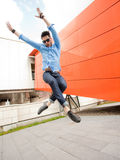 Attractive young male model jumping outdoors royalty free stock image