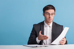Attractive young male newscaster is telling news Royalty Free Stock Image