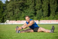 Attractive young male runner is exercising before. Cheerful athlete is sitting on green grass and smiling. He is stretching his legs and doing warm-up. There is Stock Images
