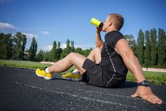 Attractive young male runner is very thirsty Stock Images