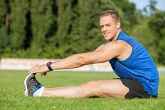 Attractive young male runner is warming up his. Handsome sportsman is sitting and stretching his legs together. He is touching sneakers with his hands. The man Stock Photography