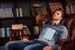 Attractive young man asleep in a library Royalty Free Stock Images