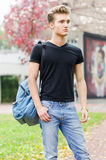 Attractive young man with back pack standing Stock Photos