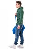 Attractive young man with bag on shoulder strap. Attractive trendy young man with bag on shoulder strap, isolated on white background, walking to left Stock Photos