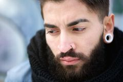 Attractive young man with beard and piercings Stock Image