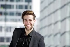 Attractive young man with beard smiling in the city Stock Photo