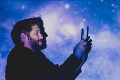 Attractive young man with beard taking pictures in a futuristic environment royalty free stock photos