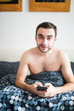 Attractive young man with a beard using a smartphone and texting while lying on his bed. Attractive man with a beard using a smartphone and texting while lying Royalty Free Stock Image